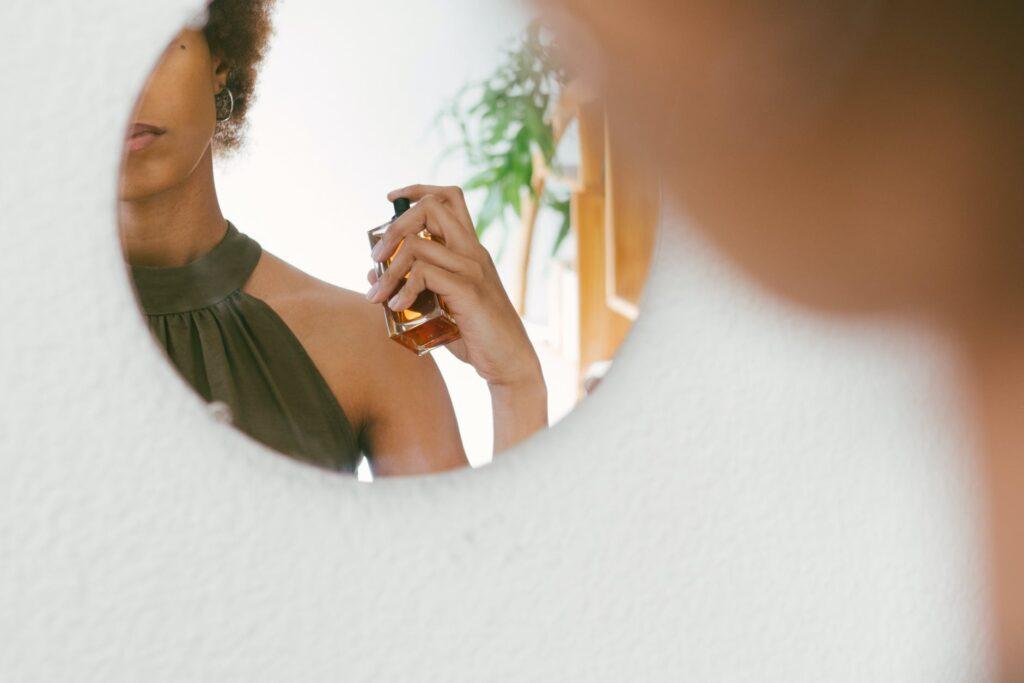 تصویری یک خانم در حال استفاده از عطر